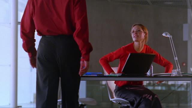 vídeos de stock e filmes b-roll de rear view ms man walking + greeting woman sitting at desk in open office - sentar se