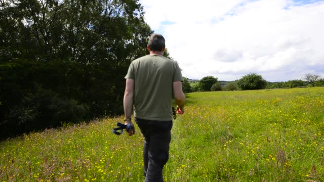 a man walking his border collie dog on a beautiful summer day - uomo maturo video stock e b–roll