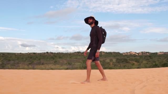 man walking in a sand dunes in jalapão state park, tocantins - zaino da montagna video stock e b–roll
