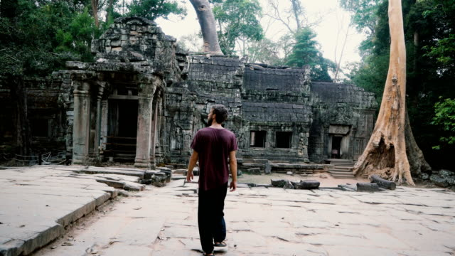 vídeos de stock e filmes b-roll de man walking   in angkor temple in cambodia - camboja