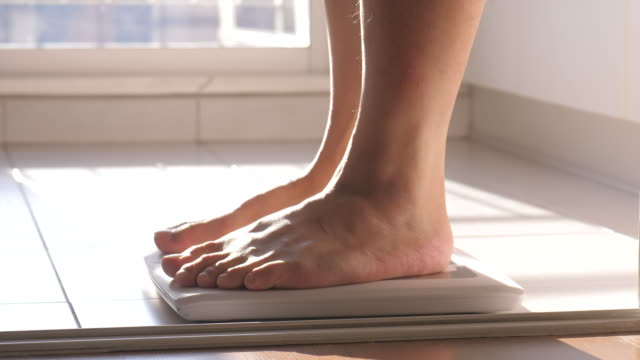man walking in body weighing scale - stepping stock videos & royalty-free footage