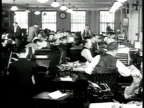 vídeos de stock e filmes b-roll de man walking in building hallway reading newspaper ws reporters typing at desks ms sign 'international news service' ms operators working teletype... - editorial