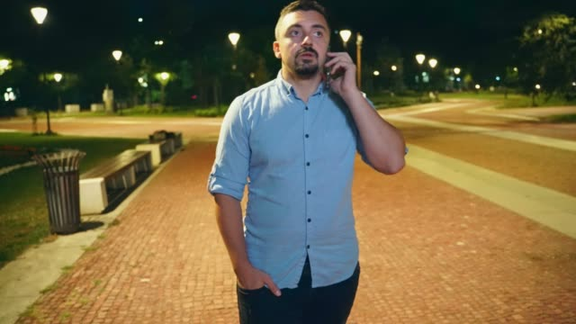 Man walking in city park at night and talking on his smart phone