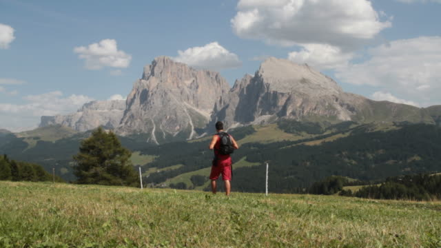 Man walking in Dolomites Sasso Lungo and Piatto on background
