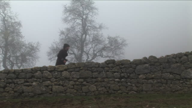 WS, PAN, Man walking in foggy landscape along stone wall, Pancorbo, Burgos, Spain