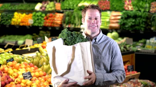 mann zu fuß in der produktion abschnitt des supermarktes - einkaufstasche stock-videos und b-roll-filmmaterial