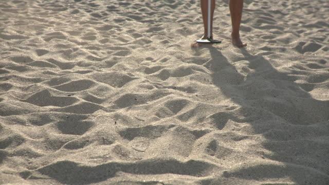 cu man walking in sand with metal detector, low section, miami beach, florida, usa - 宝探し点の映像素材/bロール