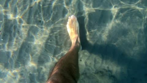 vídeos y material grabado en eventos de stock de hombre caminando en agua de mar mostrando pies sobre arena blanca - transparente