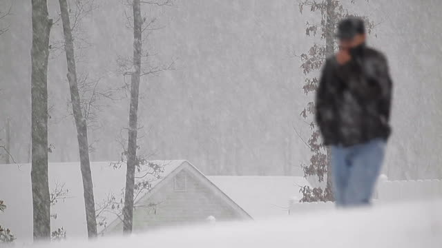 man walking in snowstorm with residential building behind in usa - only mature men stock videos & royalty-free footage