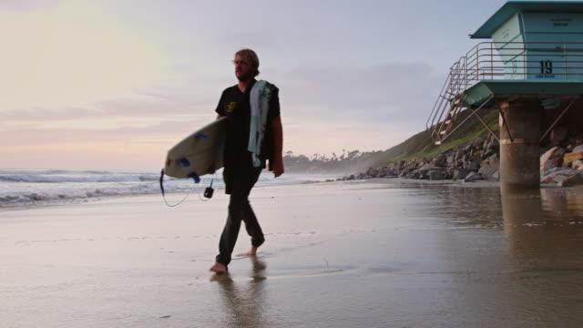 Man Walking in Surf at Sunset