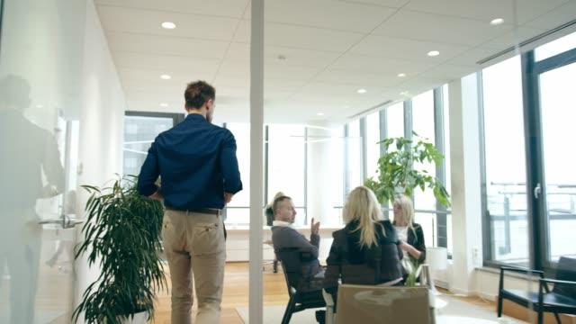 上司に報告するためにオフィスに入る男 - フリーアドレス点の映像素材/bロール