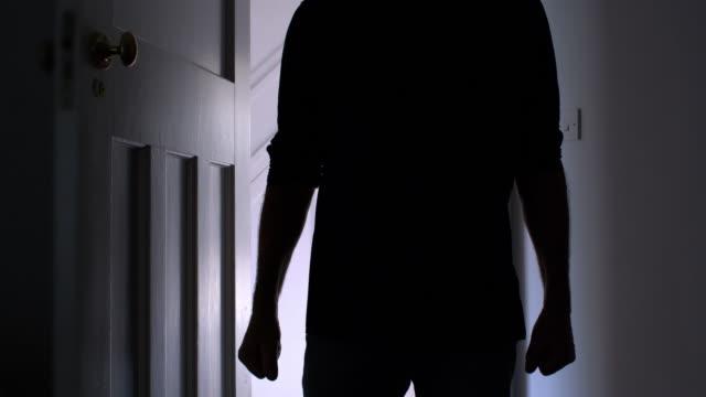 man walking into a dark room. silhouette. - doorway stock videos & royalty-free footage