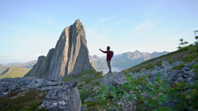 man walking near  mountain on senja island - mountain peak stock videos & royalty-free footage