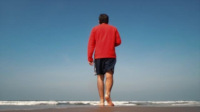 vídeos y material grabado en eventos de stock de hombre caminando en una playa - espalda humana
