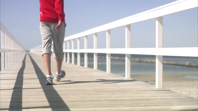 A man walking on a jetty.
