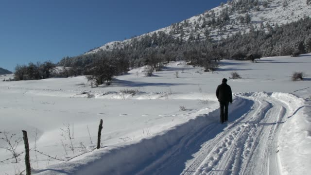 man walking on a road covered by snow near picturesque mountain village in bulgaria - pavel gospodinov stock videos & royalty-free footage