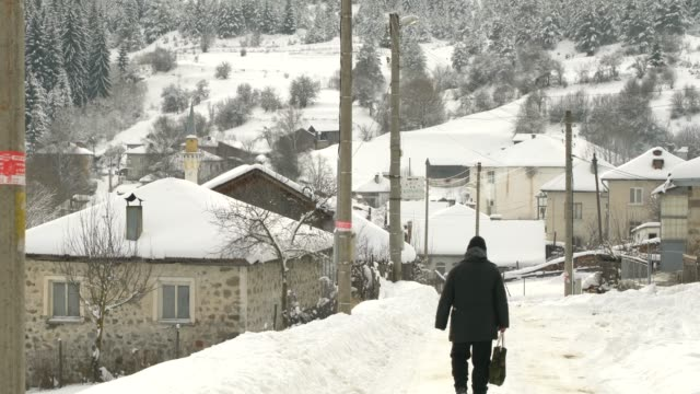 man walking on a road in a small mountain village covered by snow  in bulgaria - pavel gospodinov stock videos & royalty-free footage