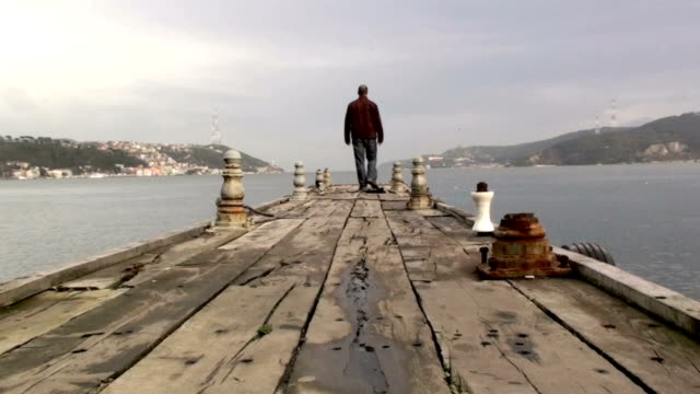 man walking on a wooden pier in cloudy day - pier stock videos & royalty-free footage