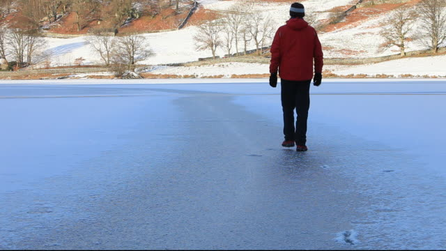 a man walking on an ice covered rydal water during a cold snap, lake district, uk. - thin stock videos & royalty-free footage