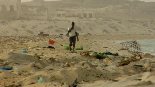 ws, man walking on beach covered with trash, nouadhibou, mauritania - mauritania stock videos & royalty-free footage