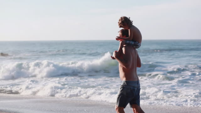 ms pan man walking on beach with boy on shoulders then takes boy off shoulders / montezuma, puntarenas, costa rica - kelly mason videos stock-videos und b-roll-filmmaterial
