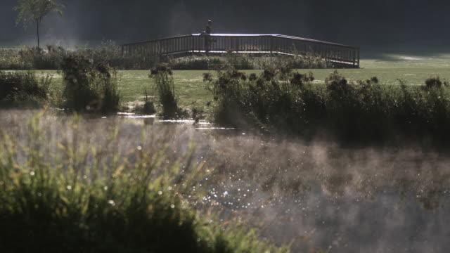 vídeos de stock, filmes e b-roll de ws man walking on bridge at garibaldi springs golf course / squamish, british columbia, canada. - bolsa de golfe