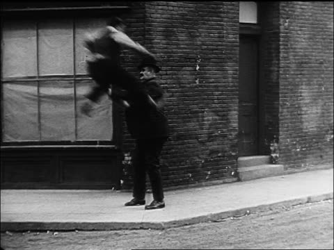 b/w 1922 man walking on city sidewalk being knocked over by flying buster keaton - buster keaton stock videos and b-roll footage