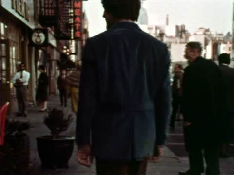 1969 rear view man walking on city sidewalk + turning to left / greenwich village, nyc - greenwich village stock videos & royalty-free footage