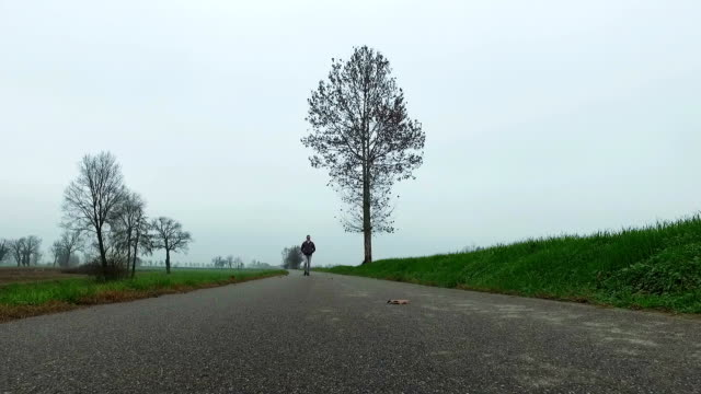 Man walking on country road in winter season