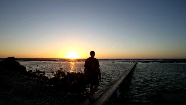 man walking on dock into sunrise on ocean. - eskapismus stock-videos und b-roll-filmmaterial