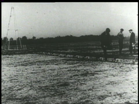 b/w 1903 man walking on early airfield runway - 1903 stock-videos und b-roll-filmmaterial