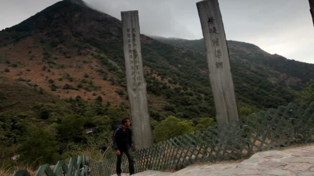 man walking on path of wisdom, lantau island hong kong - lantau stock videos and b-roll footage