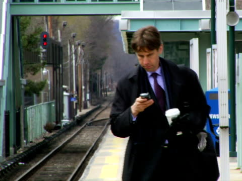vídeos y material grabado en eventos de stock de ms, man walking on railroad station platform, using mobile phone, chappaqua, new york state, usa - sobretodo