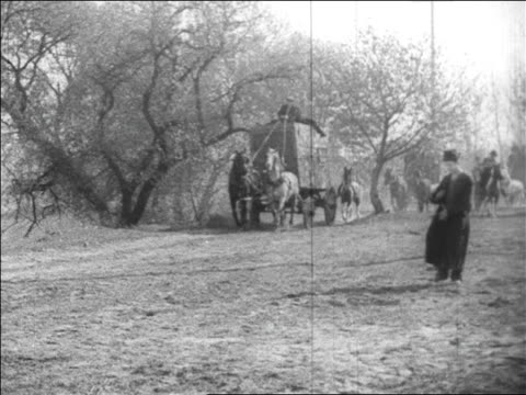b/w 1925 man (harry langdon) walking on road wiping hands / wagons + horses in background / feature - animale da lavoro video stock e b–roll