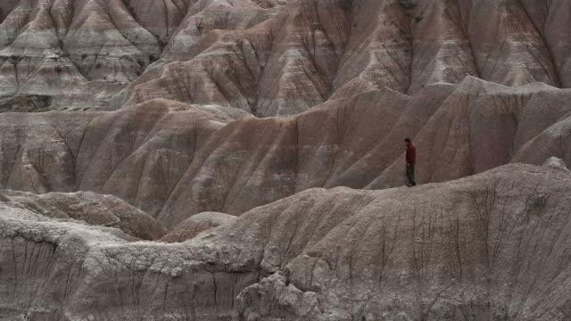 ws, pan, man walking on rock formations at badlands national park, south dakota, usa - badlands national park stock videos & royalty-free footage