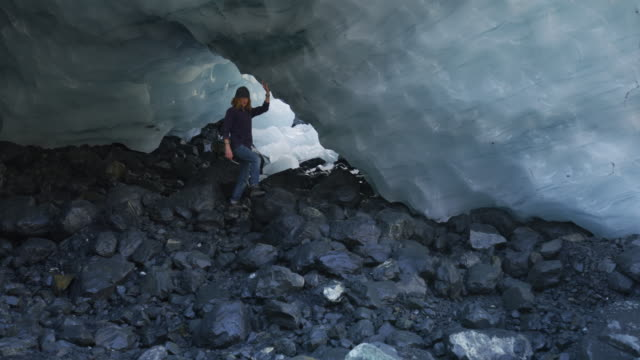 man walking on rocks under arch of glacier cave / palmer, alaska, united states - curiosity stock videos & royalty-free footage