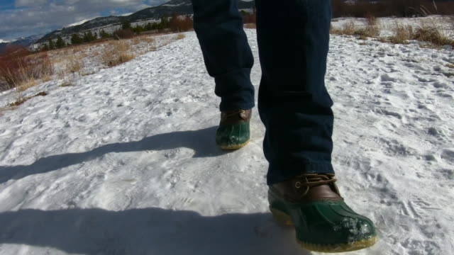 man walking on snow covered ground with winter boots - solo uomini maturi video stock e b–roll