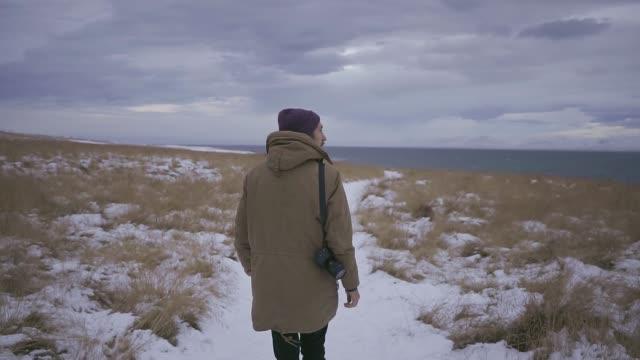 アイスランドの美しい風景を背景に歩く男 - ウィンターコート点の映像素材/bロール