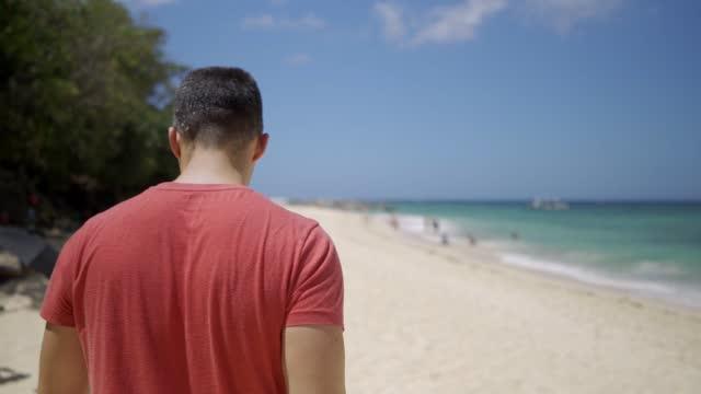 stockvideo's en b-roll-footage met mens die op het paradijsstrand loopt en foto's neemt - alleen één man