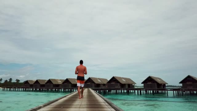 man walking on the pier over the turquoise water on the maldives - exoticism stock videos & royalty-free footage