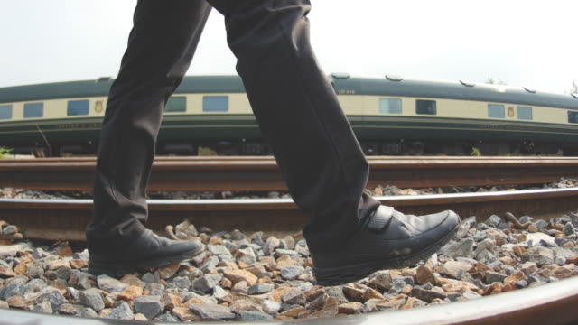 4k : man walking on the railroad. - human foot stock videos & royalty-free footage