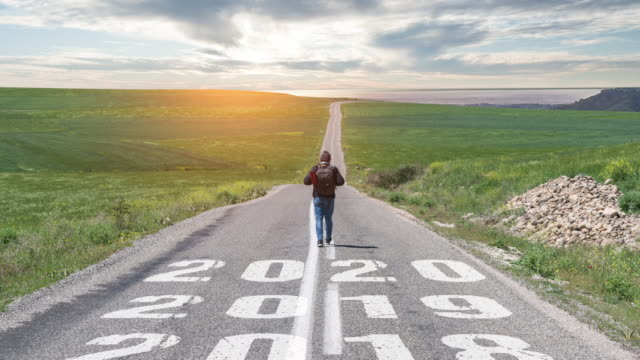 man walking on the road with writing number 2020 - forecasting stock videos & royalty-free footage