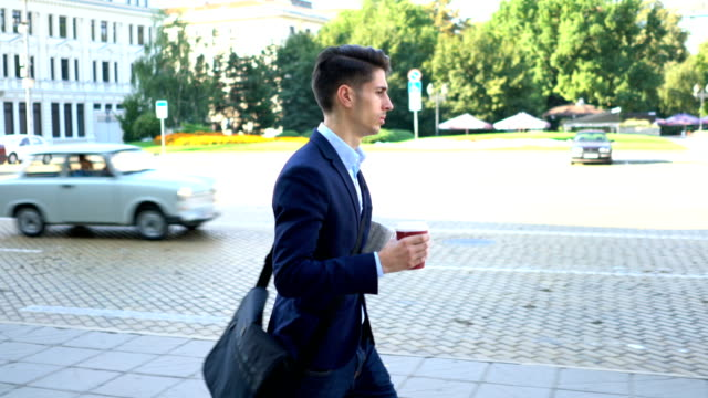 man walking on the street with coffee and newspaper. - yuppie stock videos and b-roll footage