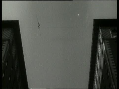 1936 B/W LA WS man walking on tightrope between buildings / Los Angeles / NO AUDIO