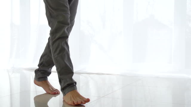 Man walking on tiled white floor