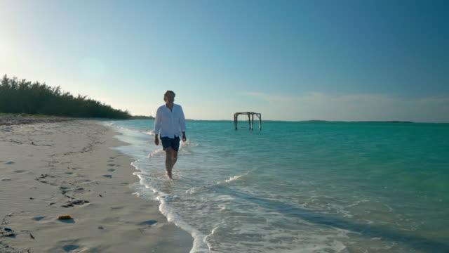 man walking on tropical beach - wide shot stock videos & royalty-free footage
