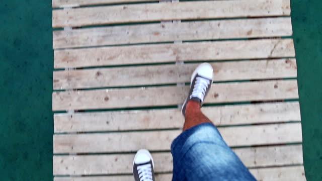stockvideo's en b-roll-footage met man lopen op houten pier, uit de hand, boven weergave - hoog standpunt