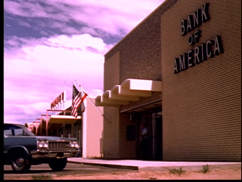 1965 ws man walking out of bank of america/ yucca valley, california - 銀行点の映像素材/bロール
