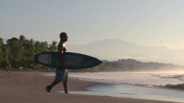 man walking out to surf