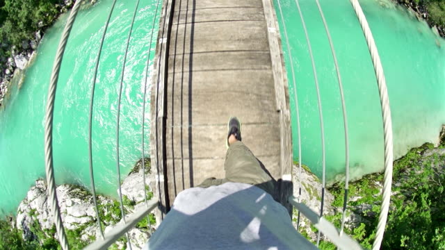 Man walking over a hanging bridge